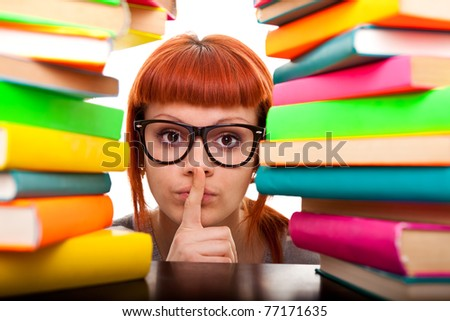 teenager peeking between stack of books with finger on mouth, silence, isolated - stock photo
