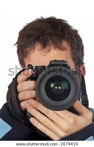 Teenager photographer holding and looking into a camera - stock photo