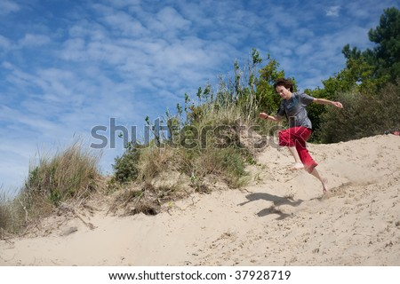 teenager playing at the seaside, running down sand-dunes - stock photo