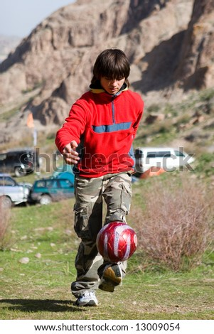 Teenager playing football (series Sport, Extreme, Mountain, Horses and Teenagers) - stock photo