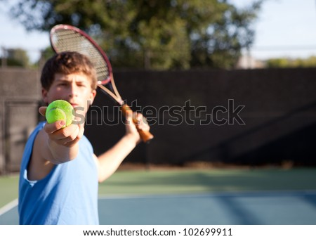 Teenager playing Tennis with determination - stock photo