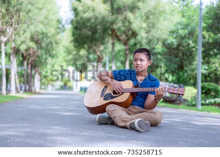 teenager playing the guitar in nature park.