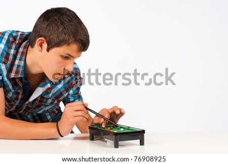 Teenager playing with a miniature snooker table - stock photo