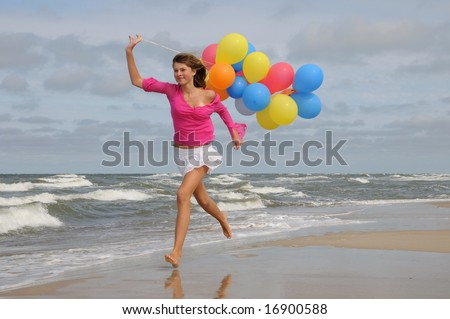 Teenager playing with balloons on the beach - stock photo
