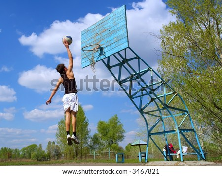 Teenager plays basketball outdoors - jumps high with ball (against sky). Shot in Ukraine. - stock photo
