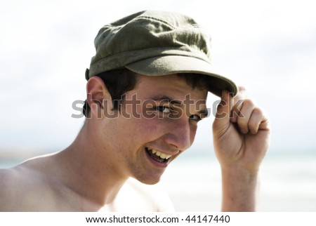 Teenager posing with hat at beach. - stock photo