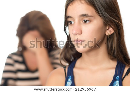 Teenager problems - Sad teenager with a serious expression and her mother crying on the background - stock photo