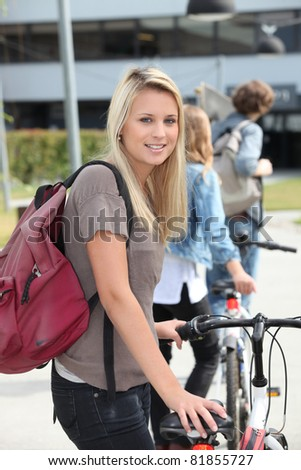 Teenager pushing bike - stock photo