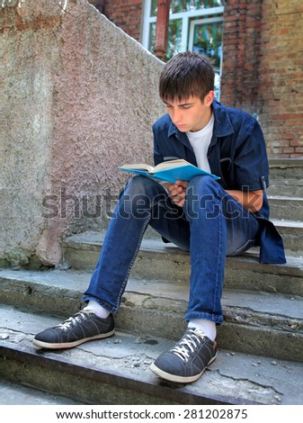 Teenager read the Book on the Landing Steps of the Old House