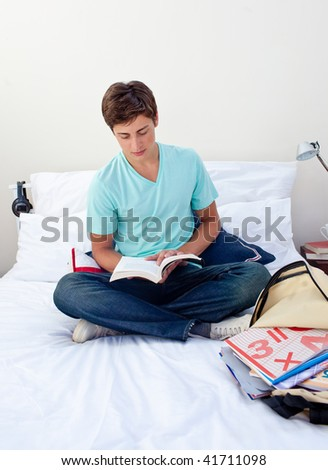 Teenager reading a book from school in his bedroom - stock photo