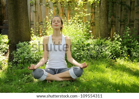 Teenager relaxing and doing yoga in a nice and quiet garden