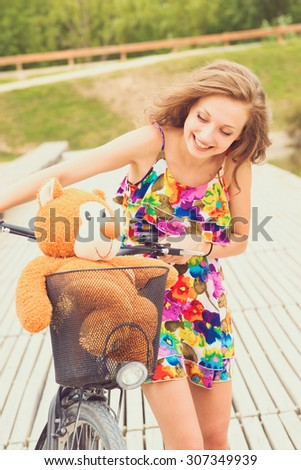 teenager riding a bicycle with her teddy bear