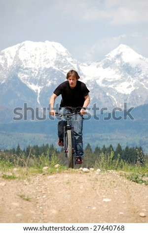 Teenager riding a bicycle with mountains in the background - stock photo