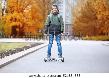 Teenager riding on gyroscooter in autumn park