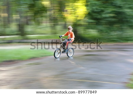Teenager riding the bicycle in motionon onbackground, horizontal