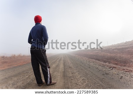 Teenager Road Mist Teenager boy standing middle mountain rural dirt road in winter morning mist