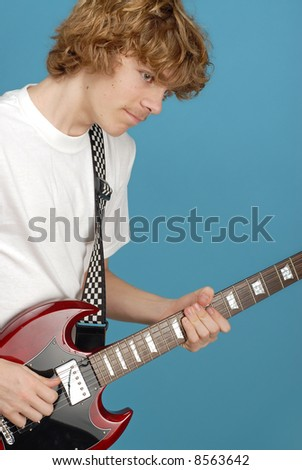 Teenager rocking out on an electric guitar on blue background