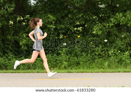 Teenager running on a footpath - stock photo
