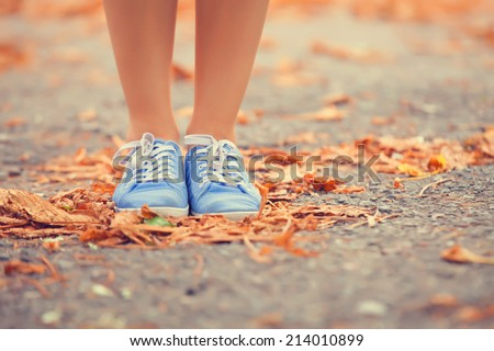 Teenager's foots in gumshoes in the park. - stock photo