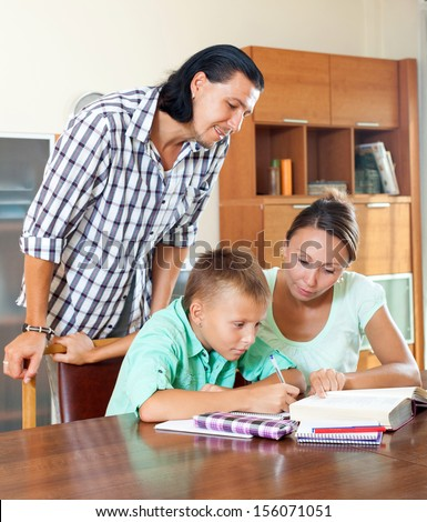 Teenager schoolboy and parents together doing homework in home