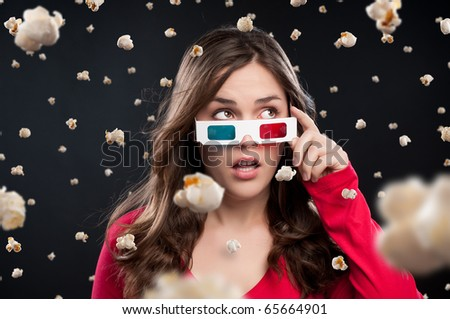 Teenager sees a shower of popcorn raining down on her in a 3D cinema - stock photo
