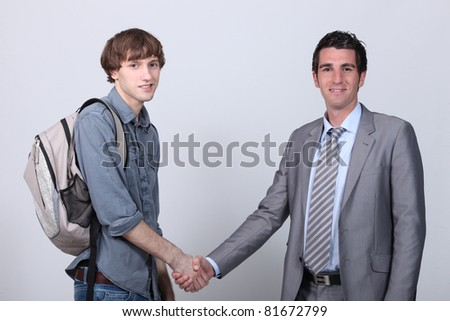 Teenager shaking hands with a man in a suit - stock photo