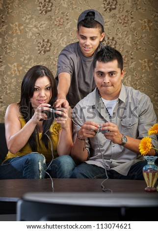 Teenager shows parents how to use video game controllers - stock photo