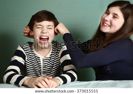 teenager sister pull her brother boy ears because of the lost bet  - stock photo