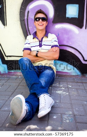 Teenager sitting against graffiti wall - stock photo