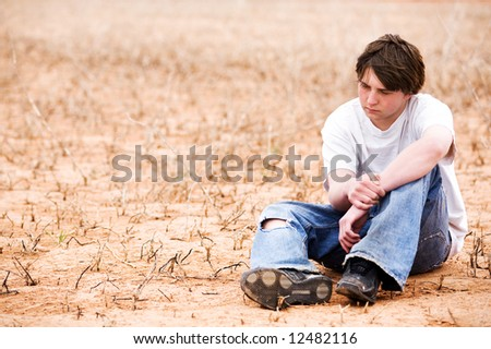 teenager sitting depressed in dry lake bed amongst the weeds, contemplating.