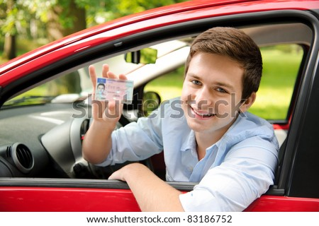 teenager sitting in new car and shows his drivers license - stock photo