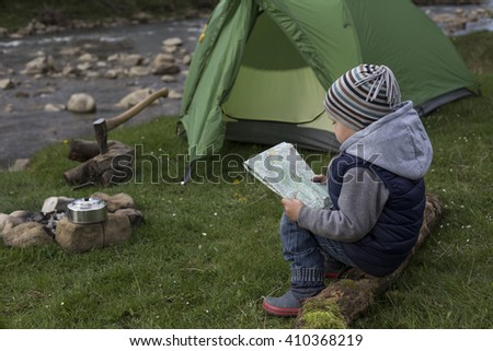 Teenager sitting near a campfire at a campsite, and looks into the camera. - stock photo