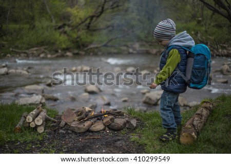 Teenager sitting near a fire in camping and watching map.