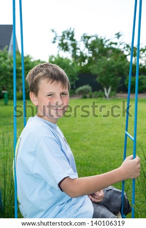 teenager sitting on a swing in the garden - stock photo