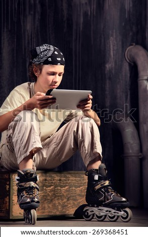 teenager sitting on box with tablet pc - stock photo