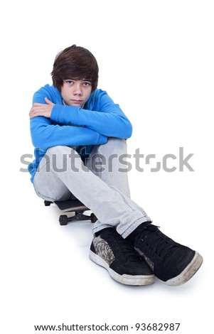 Teenager sitting on his skateboard - isolated with a bit of shadow - stock photo