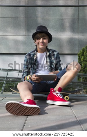 Teenager sitting on skateboard with tablet pc  - stock photo