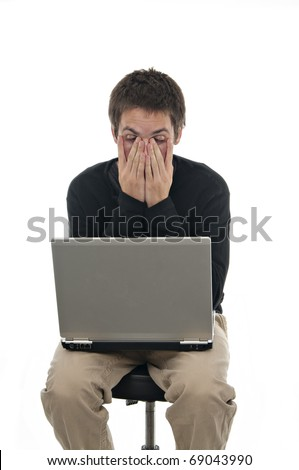 teenager sitting on stool with laptop and his hands covering his face on white background