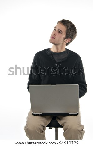 teenager sitting on stool with laptop looking up on white background - stock photo