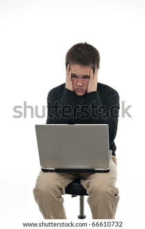 teenager sitting on stool with laptops holding his head looking confused on white background - stock photo
