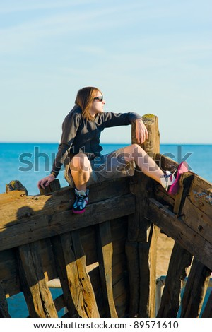 Teenager sitting on the prow of a shipwreck, a concept - stock photo