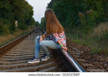 Teenager sitting on the tracks, looking into the distance and thinking