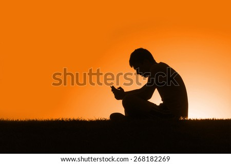 Teenager sitting sending a message with the phone - stock photo