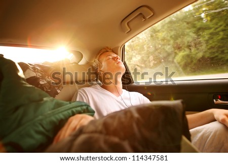 Teenager sleeping in the backseat of a car on a trip - stock photo