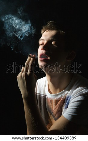 Teenager smoking a cigarette on a black background - stock photo