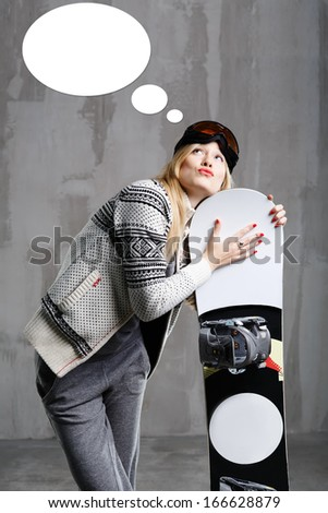 Teenager snowboarder is thinking about upcoming holiday - stock photo