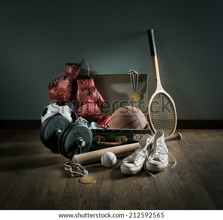 Teenager sport equipment in a vintage suitcase including sports footwear, boxing gloves, weights and baseball bat. - stock photo