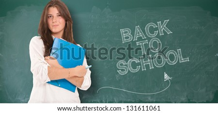 Teenager standing in front of a blackboard with back to school written on it