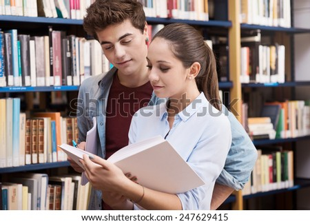Teenager students at the library studying together with books