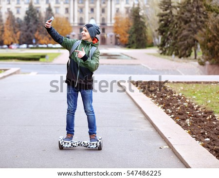 Teenager taking selfie while riding on gyroscooter in autumn park